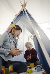 Mother playing with her son in a tent at home - KNSF03769