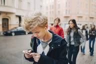 Teenage boy using mobile phone while walking with friends on sidewalk in city - MASF00372