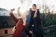 Happy young Muslim woman taking selfie with friends by railing in city - MASF00396