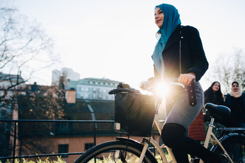 Back lit of young woman cycling by female friends against sky in city - MASF00399