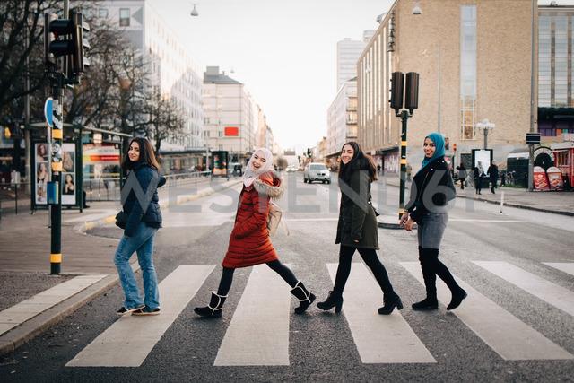 Full length of happy female friends crossing street in city - MASF00405