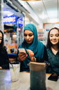 Young Muslim woman using smart phone while sitting amidst female friends in cafe - MASF00414