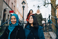 Low angle view of smiling multi-ethnic female friends moving down on staircase in city - MASF00417