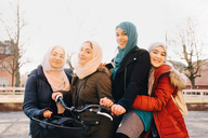 Portrait of happy multi-ethnic female Muslim friends with bicycle in city against sky - MASF00426
