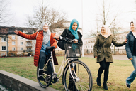 Cheerful multi-ethnic female friends walking with bicycle on grass in city - MASF00429