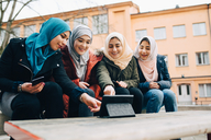 Happy female Muslim friends sitting with digital tablet on bench in city - MASF00435