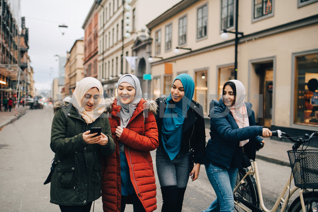 Multi-ethnic Muslim friends walking with bicycle and mobile phone on street in city - MASF00447 - Maskot/Westend61