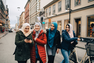 Multi-ethnic Muslim friends walking with bicycle and mobile phone on street in city - MASF00447
