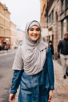 Portrait of smiling young Muslim woman wearing hijab walking on sidewalk in city - MASF00450