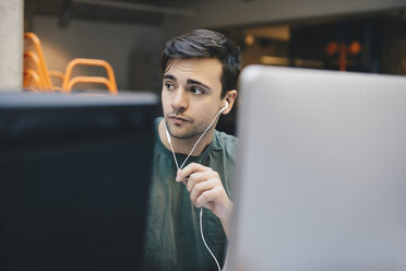 Thoughtful computer programmer wearing in-ear headphones in office - MASF00480