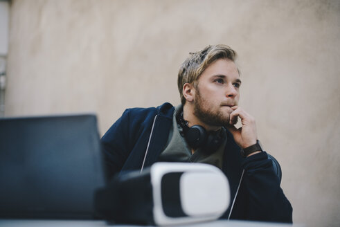 Thoughtful computer programmer looking away while sitting at desk in office - MASF00483