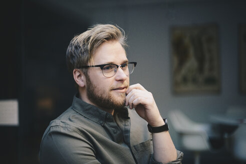 Thoughtful male computer programmer with hand on chin looking away in office - MASF00486
