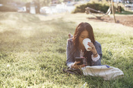 Teenage girl drinking coffee while using smart phone on grass - MASF00501