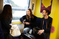 Smiling young friends traveling in yellow train - MASF00585