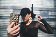 Young woman taking selfie with smart phone against glass door - MASF00606