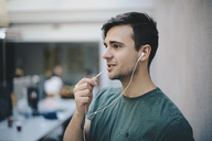 Young male computer programmer using in-ear headphones while talking in office - MASF00609