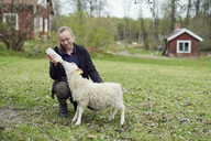 Young woman feeding milk from bottle to lamb on field - MASF00612