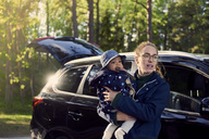 Young woman carrying baby boy while standing against car in forest - MASF00624