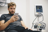 Young male patient using smart phone while reclining on bed during medical test in hospital - MASF00636