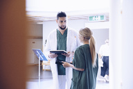 Young male doctor discussing with female nurse in hospital lobby - MASF00639