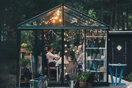 Young multi-ethnic friends enjoying dinner party in glass conservatory room at back yard - MASF00645