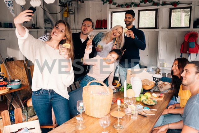 Young woman taking selfie with friends during lunch party - MASF00663