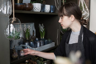 Young female entrepreneur arranging decorations on shelf at store - MASF00690