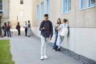 Young man using mobile phone while walking at campus with students standing in background - MASF00708