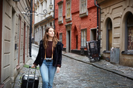 Young woman looking away while walking with luggage in alley - MASF00717