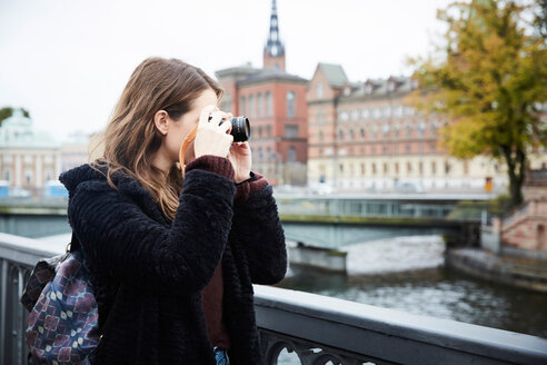 Young woman photographing through camera while standing on bridge in city - MASF00720