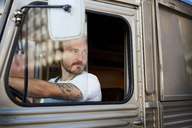 Young man looking out the window while driving food truck in city - MASF00726