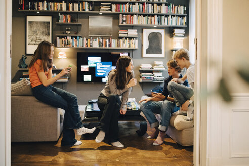 Friends talking and using mobile phone while sitting in living room at home - MASF00732