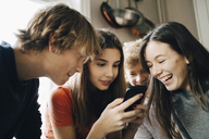 Close-up of cheerful friends looking at mobile phone in kitchen - MASF00738