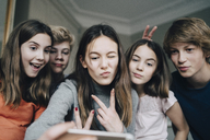 Cheerful friends taking selfie through mobile phone at home - MASF00753