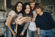 Happy friends taking selfie through smart phone while standing at home - MASF00756