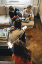 High angle view of friends using smart phone while sitting in living room - MASF00774
