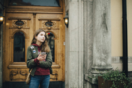 Thoughtful girl holding mobile phone while standing against building - MASF00807