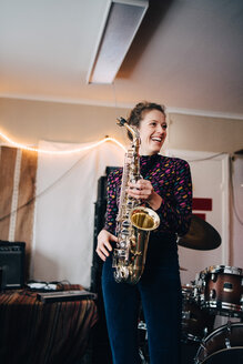 Happy young female musician playing saxophone in rehearsal studio - MASF00861