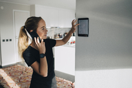 Teenage girl talking on smart phone while using digital tablet mounted on white wall at home - MASF00909