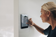 Blond woman adjusting thermostat using digital tablet mounted on white wall at home - MASF00912