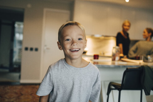 Portrait of smiling boy standing against family in background - MASF00918