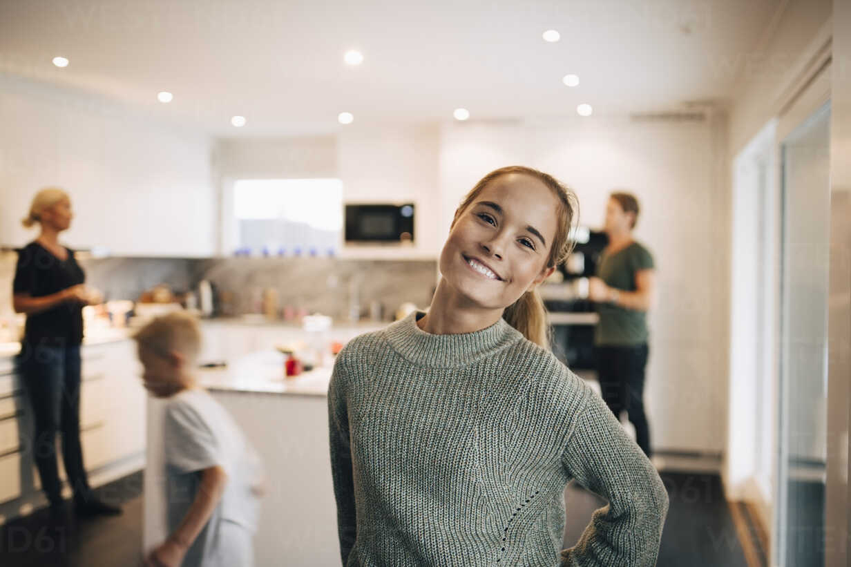 Portrait of smiling teenage girl standing against family in kitchen - MASF00924 - Maskot/Westend61