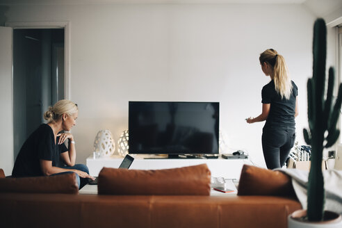 Woman using laptop while teenage daughter standing by television set in living room at home - MASF00948