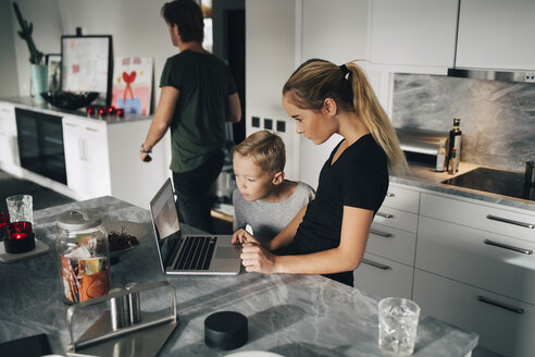 High angle view of boy standing by sister using laptop at kitchen island - MASF00969