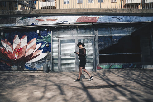 Side view of young woman using mobile phone while walking on footpath by building - MASF00990