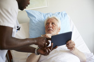 Senior man looking at male nurse while using digital tablet on bed in hospital ward - MASF01014