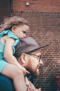 Side view of mid adult man carrying daughter on shoulders against brick wall - MASF01035