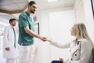 Side view of female patient shaking hands with young male nurse in hospital - MASF01044