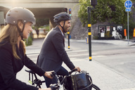 Side view of smiling business coworkers cycling in city - MASF01062