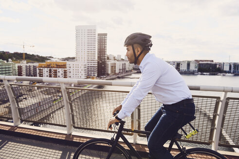 Side view of man cycling on footbridge against sky - MASF01065